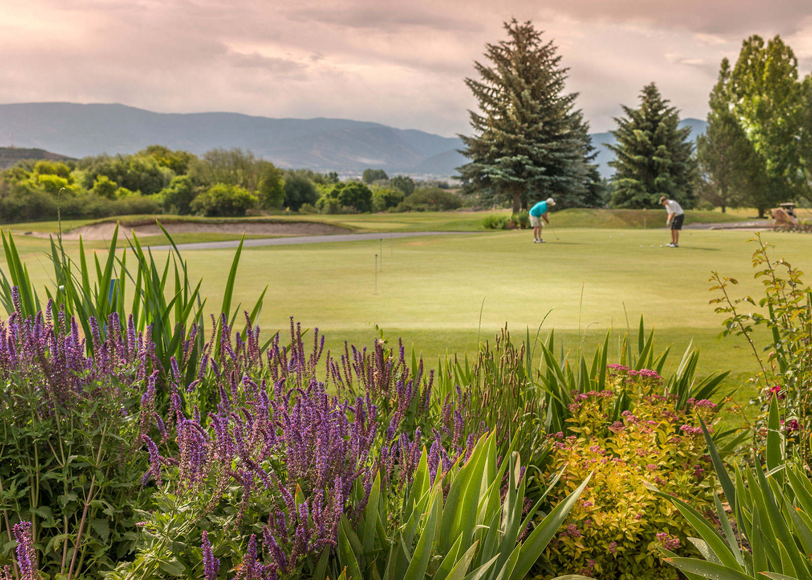 Gorgeous landscaping in the foreground as two men put at the Crater Springs golf course