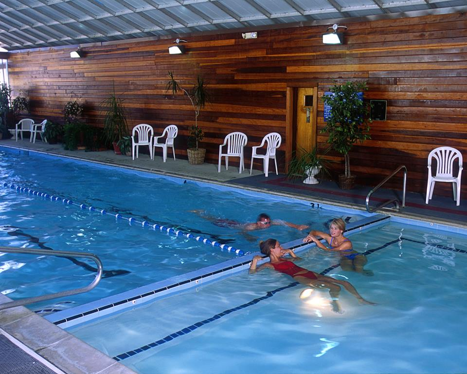 Two women relax in the hot tub while a man swims laps at Homestead Resort