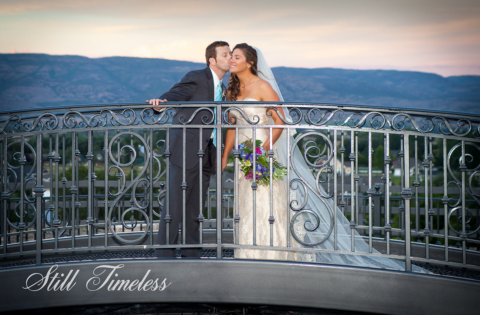 Groom kissing the bride on the cheek on the bridge above the crate with the Heber valley in the background