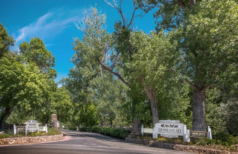Entrance to the Homestead Resort on a blue bird summer day in Heber, Utah surrounded by towering trees