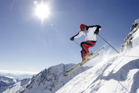 Male in a white jacket and red and black ski pants skiing on a bluebird day near the Homestead Resort
