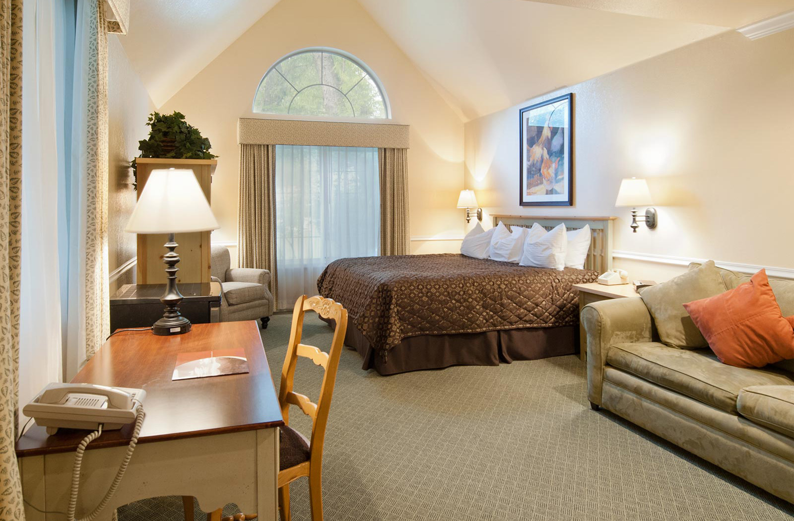 One of our well appointed hotel suites in Midway with bed, couch, desk and more
