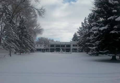 Snow covered Homestead Resort from the parking lot with lawn and fountain in front