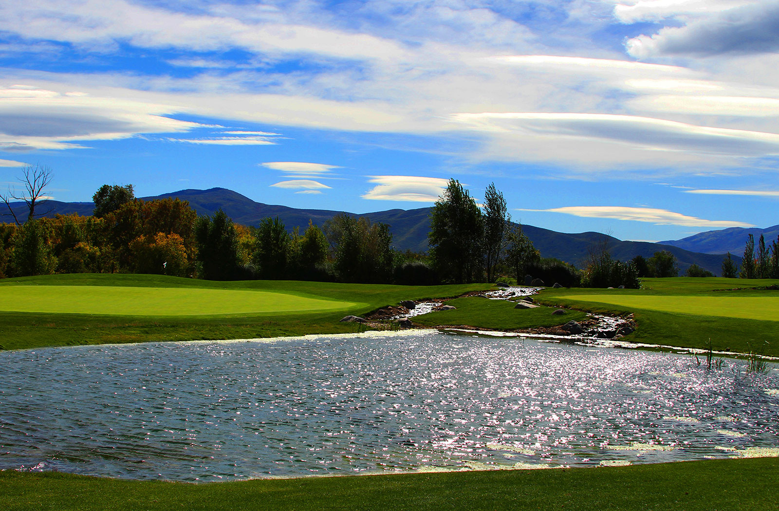 A pond separates two golf greens at Crater Springs golf course at the Homestead