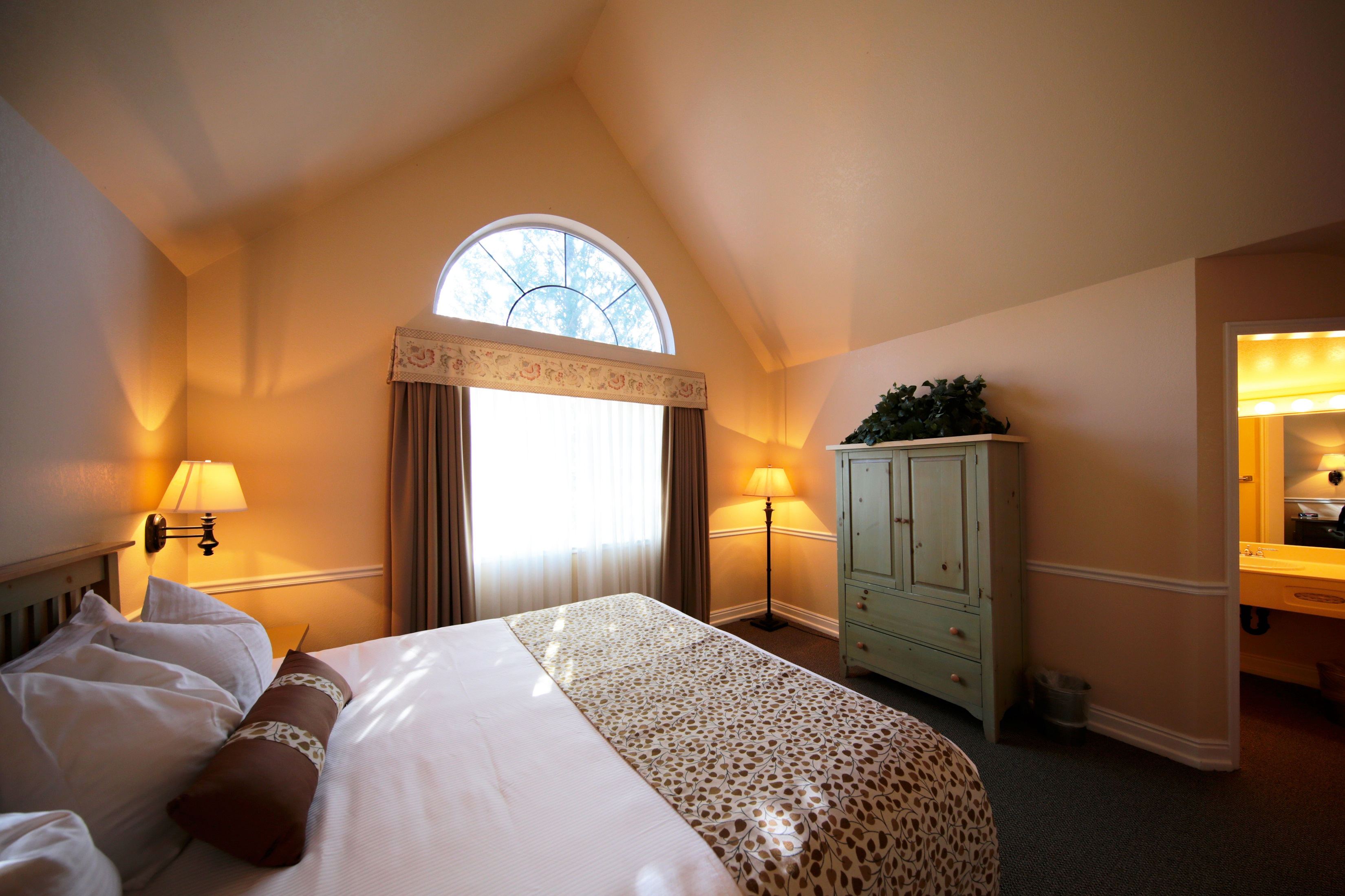 Picture of Homestead's Cottage King Guestroom. The room contains a king size bed, a stylish dresser and private restroom. A large window allows for natural light to illuminate the room.