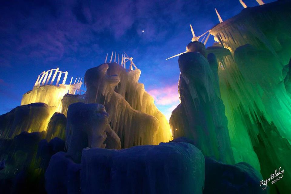 Ice castles lit up with green & yellow lights with the evening sky in purples, pinks & light blue at the Homestead