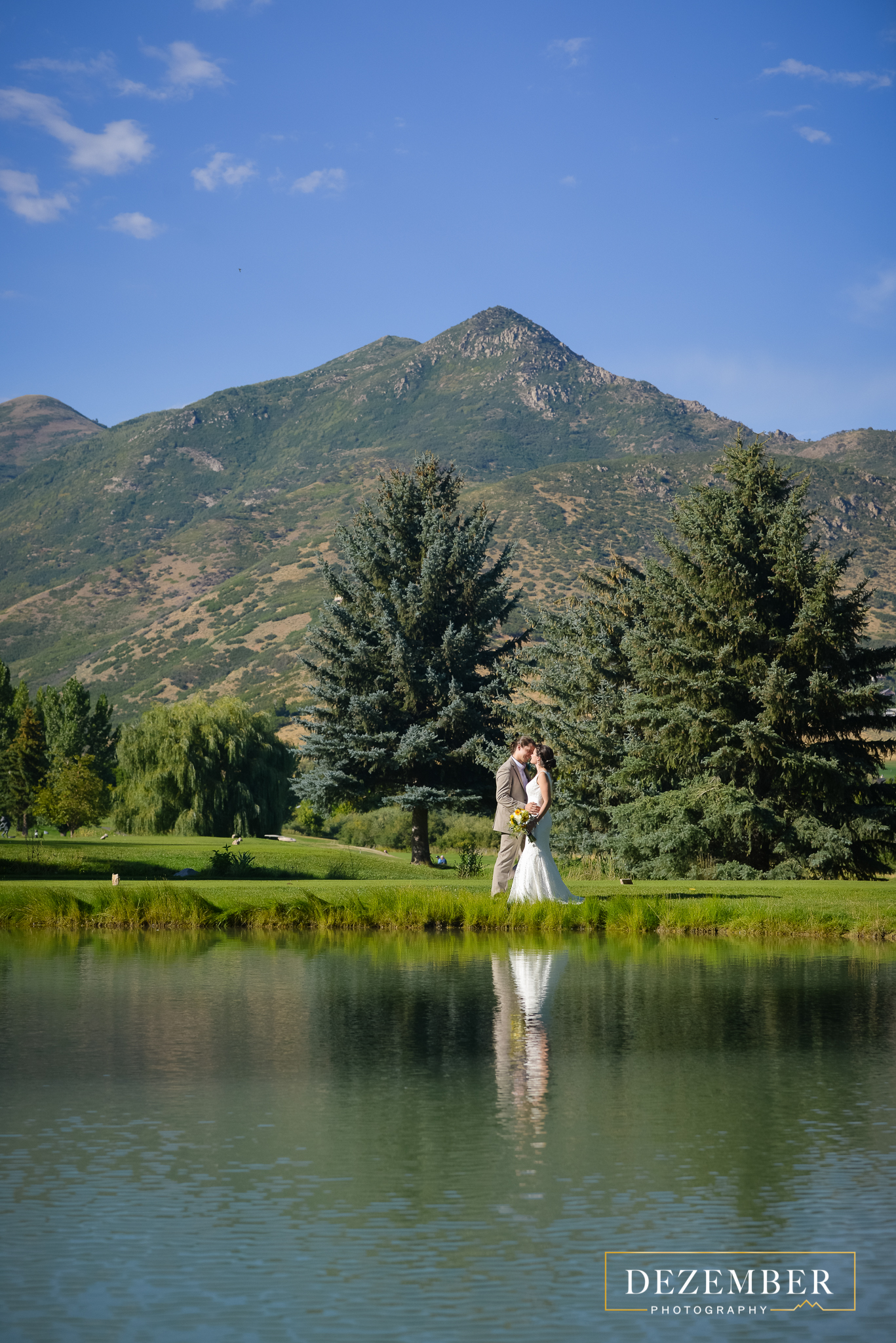 Birde and Groom Kissing by the Outdoor Pond on the Crater Springs Golf Course