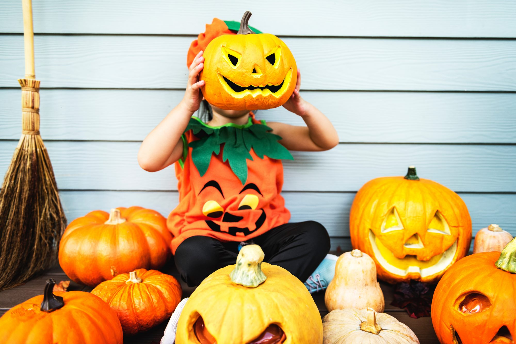 Child with carved pumpkins playing