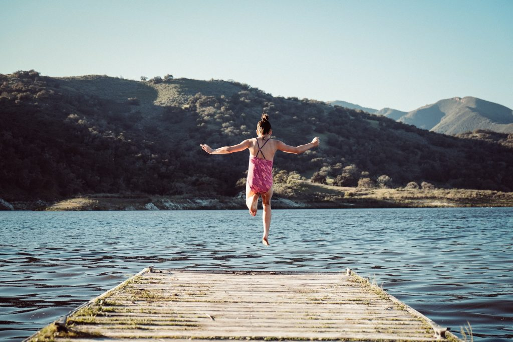 Young girl jumps off the dock into the lake near our Utah resort